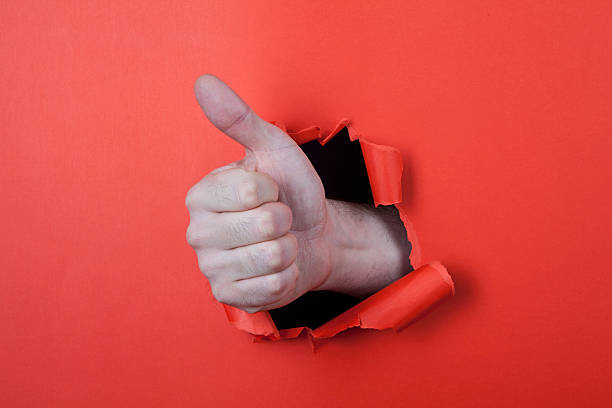 Hand through hole on the red paper. stock photo