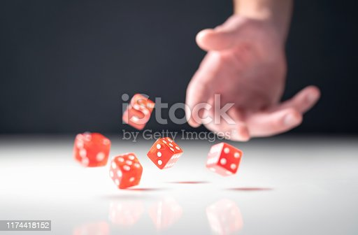 Hand throwing and rolling dice. Gambler tossing five red poker and casino dice on table. Man gambling or playing board game. Risk, luck, betting or addiction concept.
