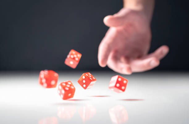 Hand throwing and rolling dice. Gambler tossing five red poker and casino dice on table. Man gambling or playing board game. stock photo