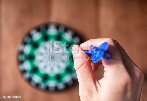886643538 istock photo Hand throwing dart arrow to dartboard 1018138348