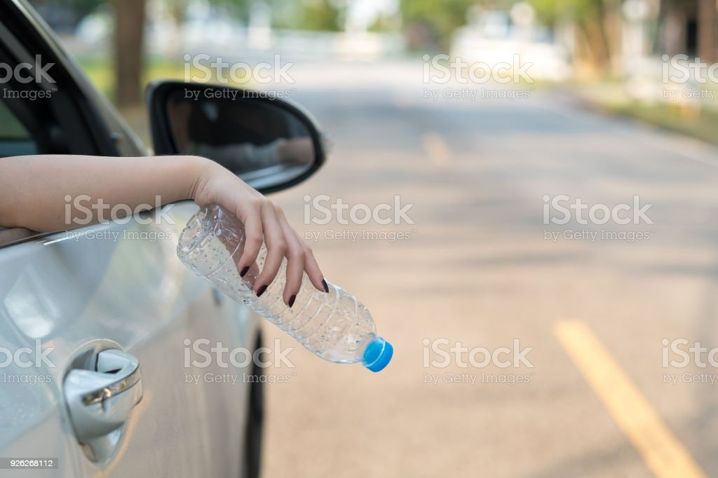 Hand throwing plastic bottle on the road stock photo