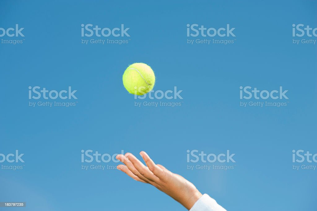 Hand throwing up a tennis ball stock photo