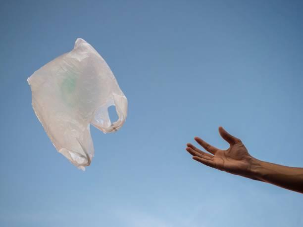 eine hand wirft weiße plastiktüte in die luft mit blauem himmel hintergrund. - windbeutel stock-fotos und bilder