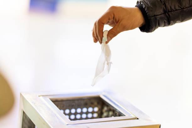 Hand wirft weißes Gewebepapier in einen Papierkorb – Foto