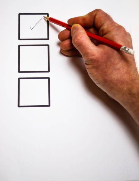 Hand ticking a box with pencil stock photo