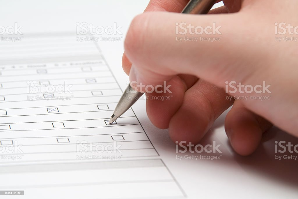 Hand ticking boxes on a questionnaire form stock photo