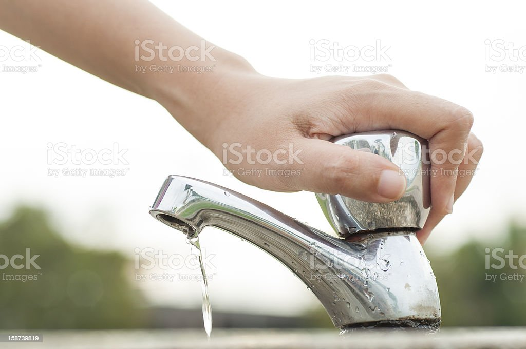Hand tightly closing a water faucet outdoors stock photo