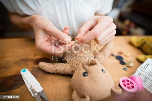 Hand to fix a stuffed toy bear
