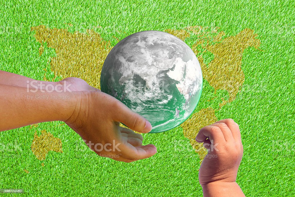 hand to reach the world for children on the grass stock photo