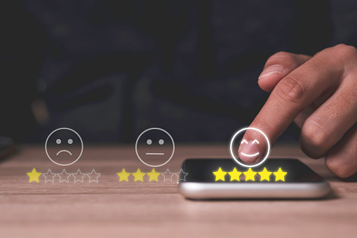 Hand touch on mobile phone to add five yellow stars to customer evaluates products and services. Customer satisfaction and marketing survey rating concept.