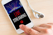 Hand touch smart phone and ear phone with Live Streaming word on wood table ,Internet marketing concept