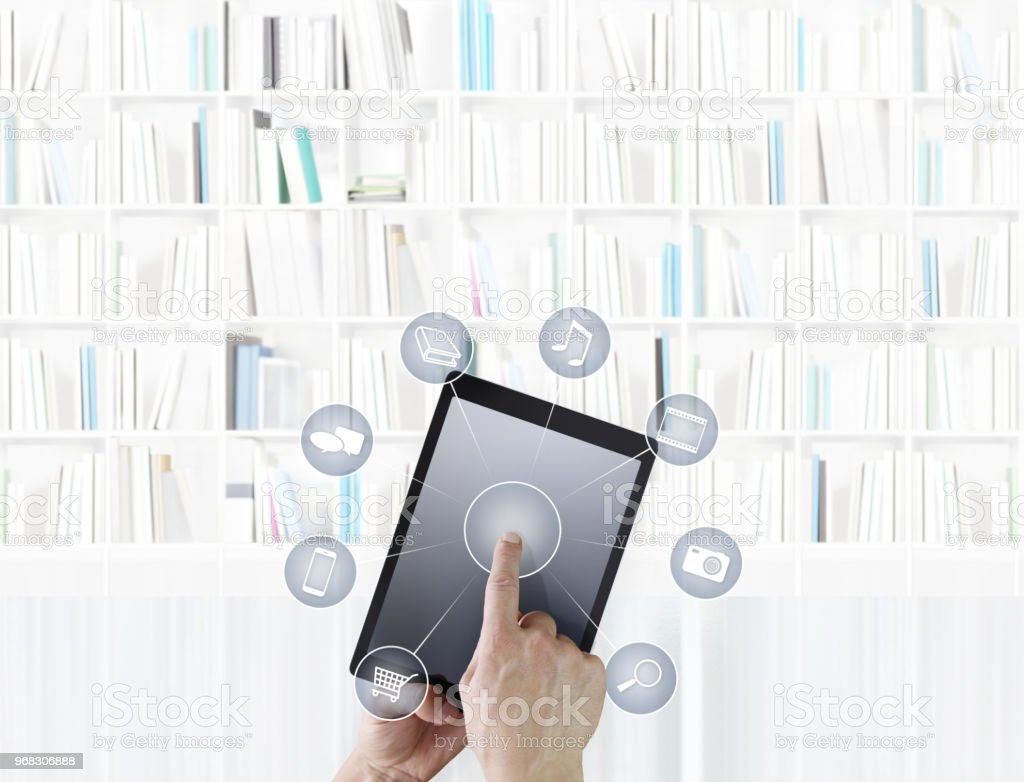 hand touching digital tablet with icons isolated on library background stock photo