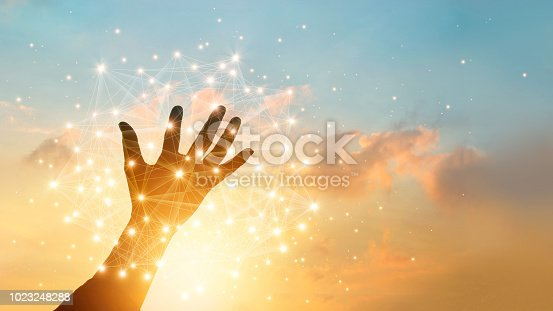 Hand touching global network connection and data exchanges on sky sunset background. Technology and telecommunication concept.