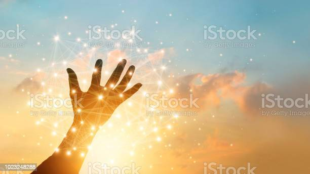 Photo of Hand touching global network connection and data exchanges on sky sunset background. Technology and telecommunication concept.