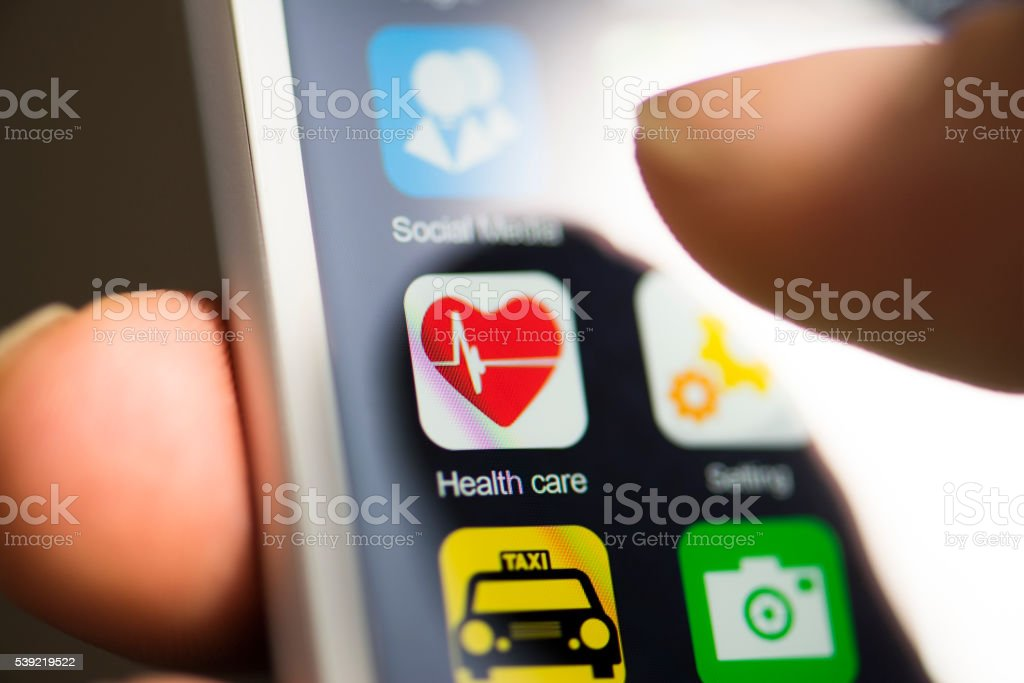 Hand touching healthcare app on screen stock photo