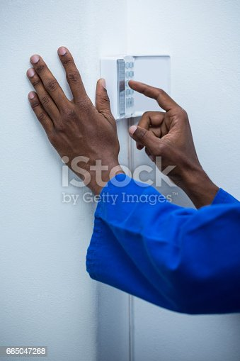 istock Hand touching home security keypad 665047268