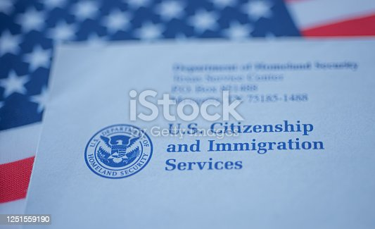 Hand touching Letter (Envelope) from USCIS on  flag of USA background. Close up view.