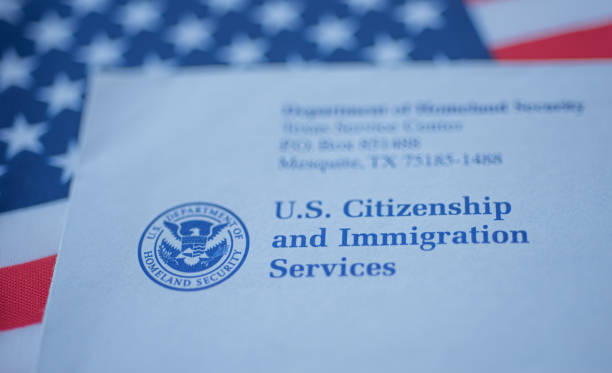 Hand touching Letter (Envelope) from USCIS on  flag of USA background. Hand touching Letter (Envelope) from USCIS on  flag of USA background. Close up view. department of homeland security stock pictures, royalty-free photos & images