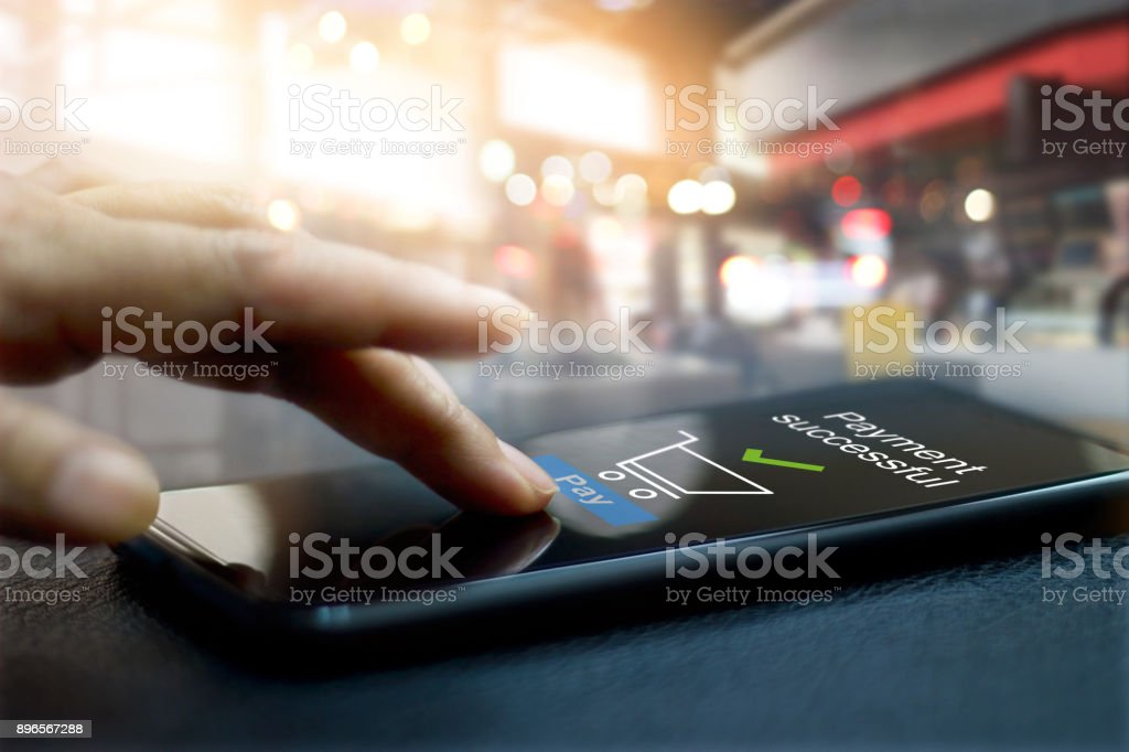 Hand touching mobile screen of a Payment successful message on shopping mall background stock photo
