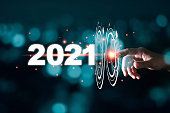 istock Hand touching pass thru infographic to 2021 year with blue bokeh and dark background. New year change concept. 1213868775