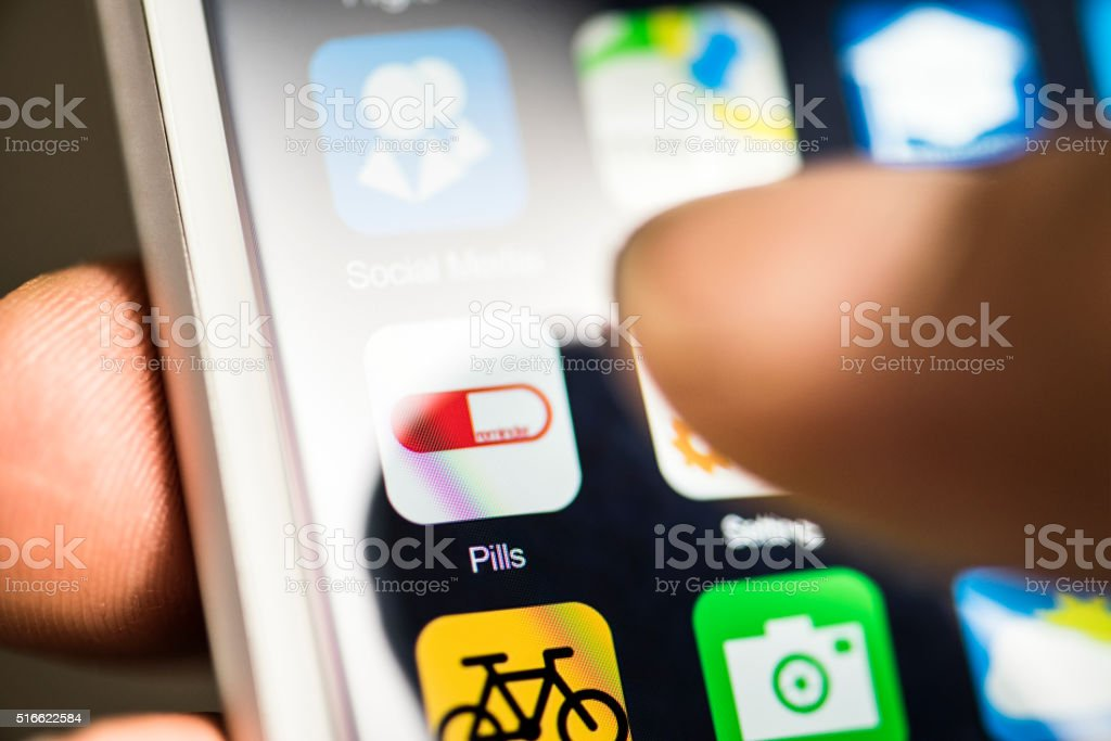 Hand touching pill reminder app on screen stock photo