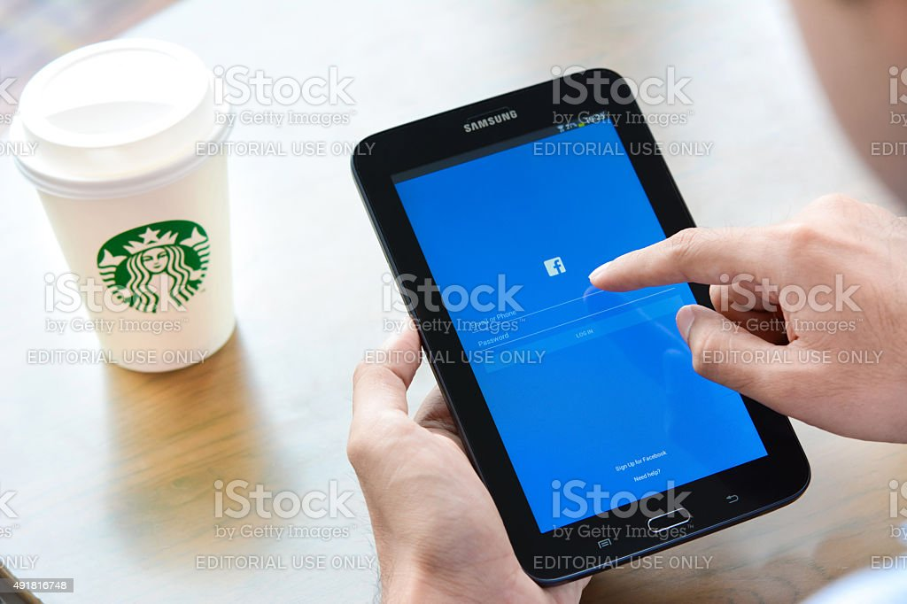 Hand touching Samsung Galaxy tablet screen, opening facebook page stock photo