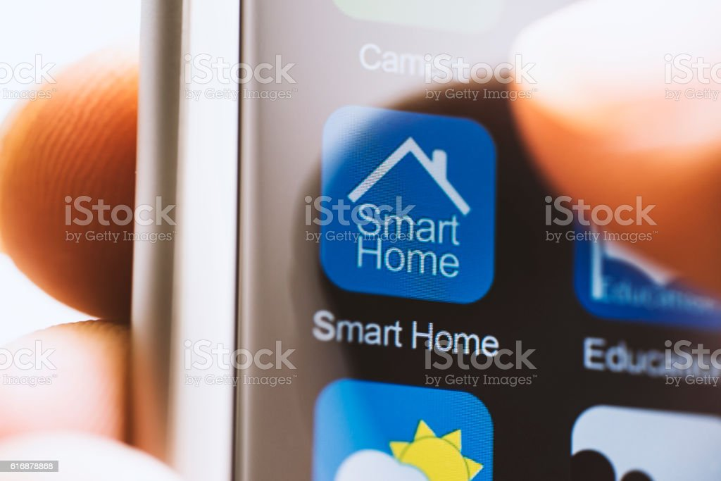 Hand touching smart house app on screen stock photo