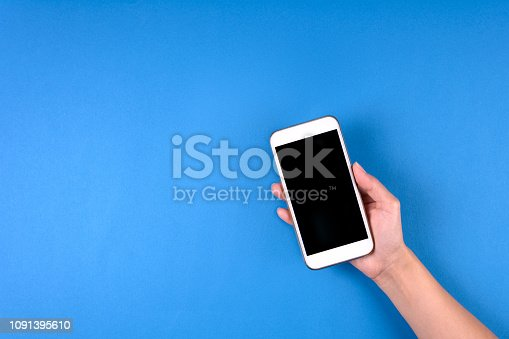 Hand touching smartphone screen on blue background. Mock-up. Top view. Copy space