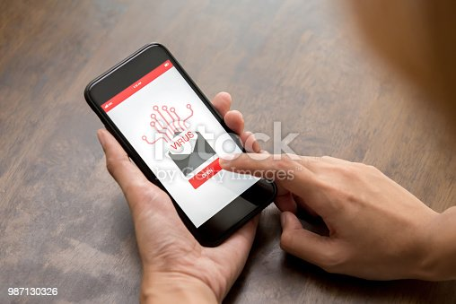 1008108222 istock photo Hand touching smartphone screen to open email that contains virus 987130326