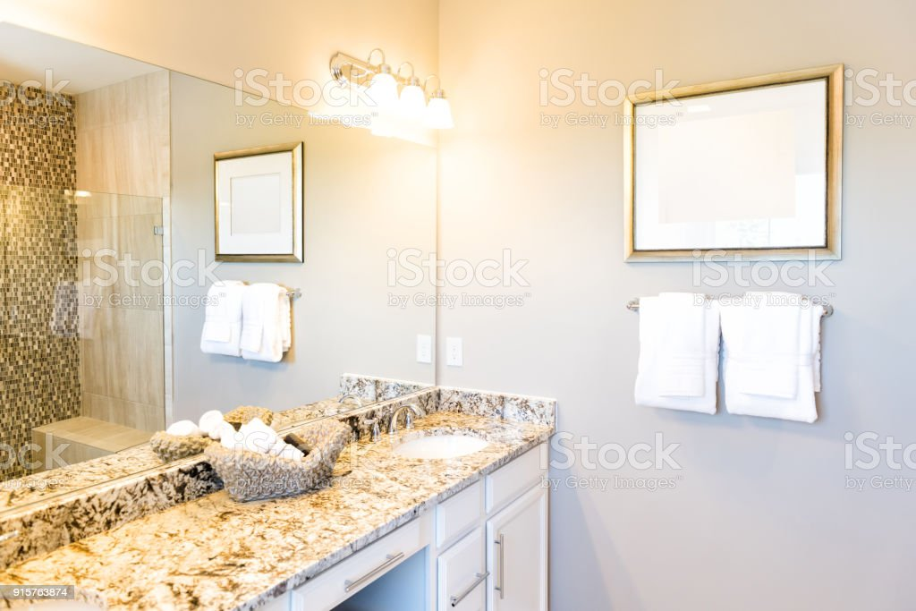 Hand Towels In Woven Basket In Bathroom Granite Countertop With Sink And  Mirror In Staging Model
