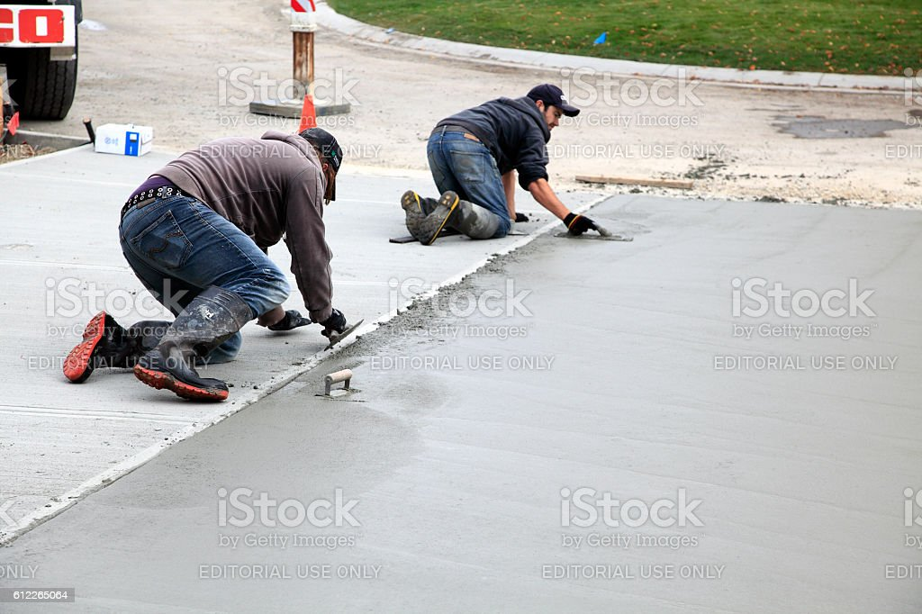 Hand Troweling New Residential Concrete Driveway stock photo