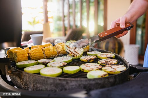 Cooking vegetables on barbeque grill with zucchini slices, corn cobs, turn with metal tongs, asian street food market
