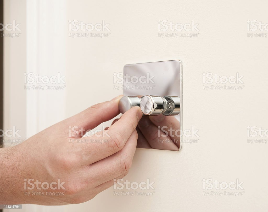 hand turning a light dimmer switch royalty-free stock photo