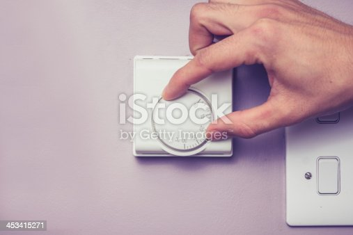 istock Hand turning dial on thermostat 453415271
