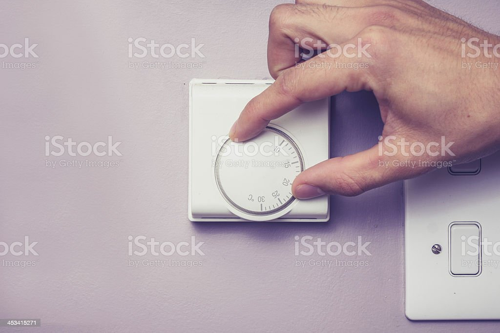 Hand turning dial on thermostat stock photo