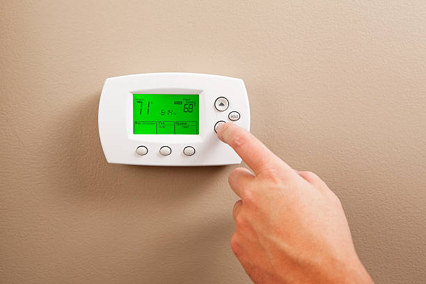 Hand Turning Down Digital Programmable Thermostat stock photo