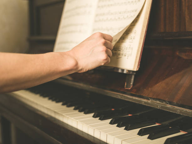 hand turning music paper at piano - piano noten stock-fotos und bilder
