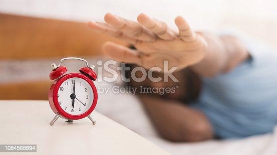 istock Hand turning off alarm clock waking up at morning 1084565894