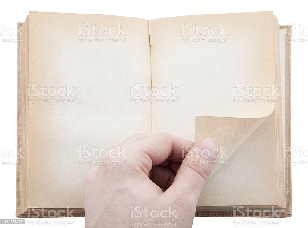Hand turning old blank book page. Clipping path included. stock photo