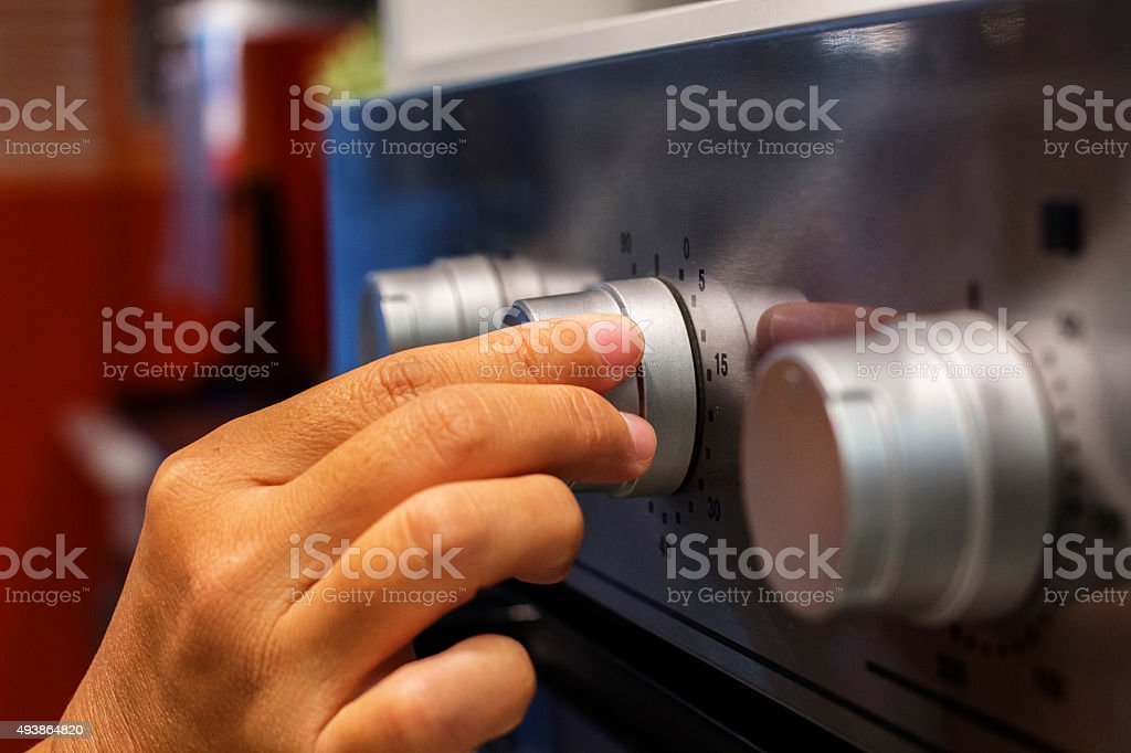 hand turning on a knob on microwave oven stock photo