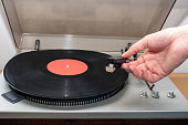istock Hand turning on stereo turntable analog retro vintage. An old-fashioned plastic turntable playing a music track 1341992399