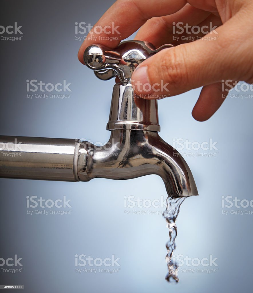 Hand turning silver tap with water dripping out stock photo