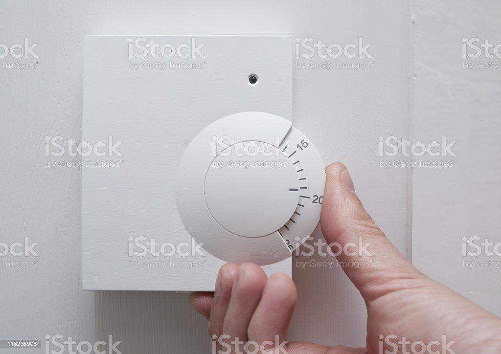 Hand turning thermostat stock photo