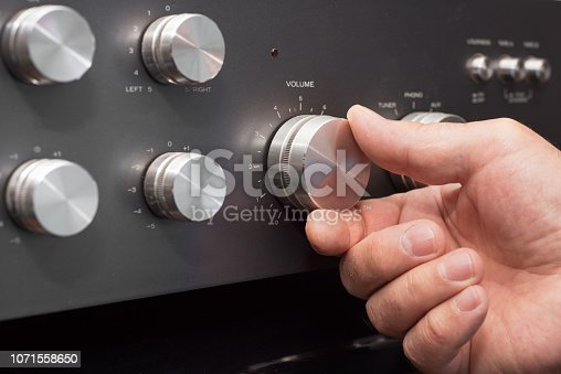 istock Hand turning up the volume in a stereo 1071558650