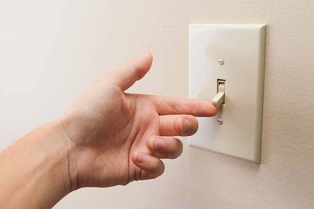 hand turning wall light switch off - 2015 stok fotoğraflar ve resimler