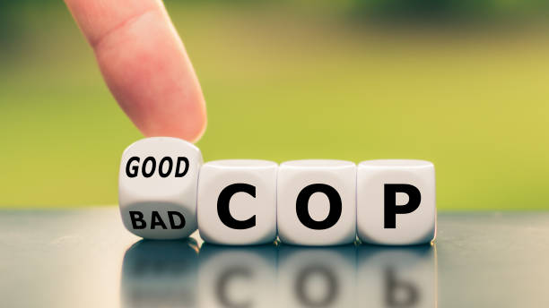 """Hand turns a dice and changes the expression """"bad cop"""" to """"good cop"""", or vice versa. stock photo"""