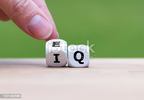 """istock Hand turns a dice and changes the expression """"IQ"""" (Intelligence Quotient) to """"EQ"""" (Emotional Intelligence/Quotient). 1201462590"""