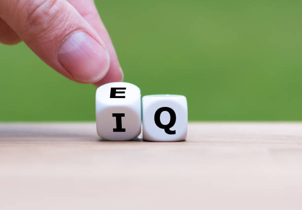 """hand turns a dice and changes the expression """"iq"""" (intelligence quotient) to """"eq"""" (emotional intelligence/quotient). - intelligence стоковые фото и изображения"""