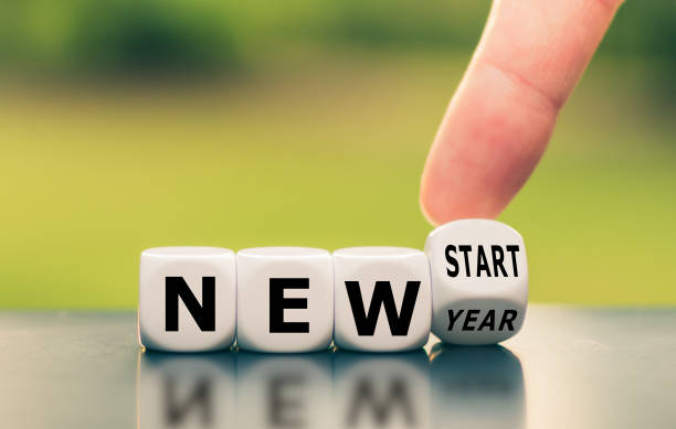 """Hand turns a dice and changes the expression """"new year"""" to """"new start"""". stock photo"""
