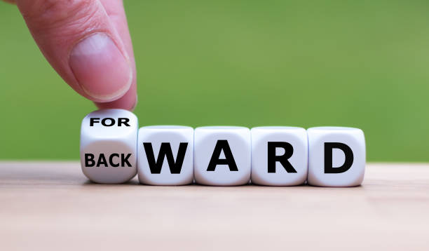 "Hand turns a dice and changes the word ""BACKWARD"" to ""FORWARD"". Hand turns a dice and changes the word ""BACKWARD"" to ""FORWARD"". bending over backwards stock pictures, royalty-free photos & images"